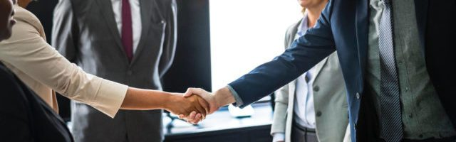 business owners shaking hands during sales training program