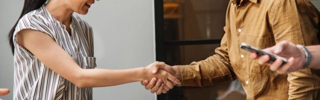 man and woman shaking hands after meeting during a sales training course