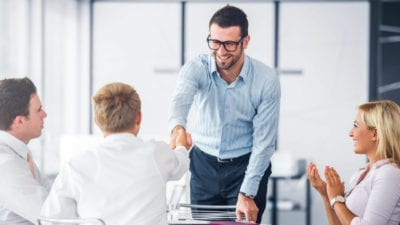 man shaking hands at sales training program