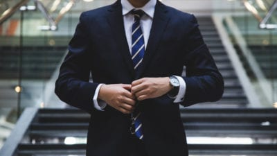 business man buttoning up his suit after sales training program